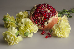 Grenades and cloves. Still life pomegranate yellow carnations. Red sugary juicy  fruit in fragrant flowers. Nature Stock Photo