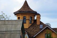 grenier de brique avec des fenêtres et une tour avec un toit carrelé contre le ciel et les nuages image libre de droits
