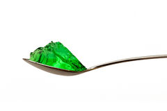 Grenn jello on teaspoon. Isolated Stock Photos