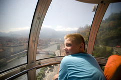 Grenoble cable car. Grenoble, France. Boy sitting in the famous cable car leading to Bastille, looking at cityscape Royalty Free Stock Photos