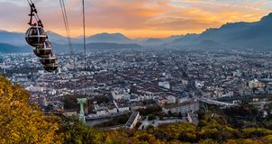 Grenoble en kabelwagens in de zonsondergang stock foto's