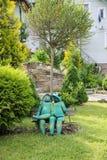 Grenouilles drôles décoratives se reposant sur le banc en parc de ville de Schodnic Photos stock