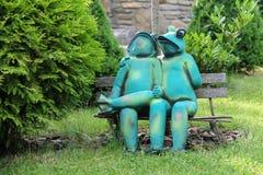 Grenouilles drôles décoratives se reposant sur le banc en parc de ville de Schodnic Image libre de droits