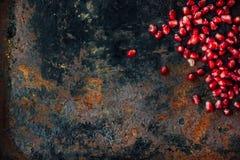 Grens van granaatappelzaden wordt gemaakt over zwarte rustieke achtergrond die Royalty-vrije Stock Afbeeldingen
