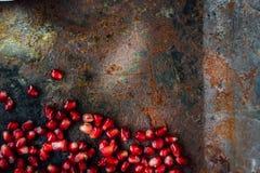 Grens van granaatappelzaden wordt gemaakt over zwarte rustieke achtergrond die Stock Fotografie