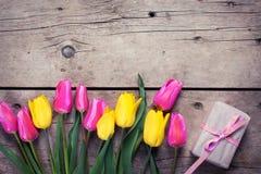 Grens van heldere gele en roze de lentetulpen en doos met PR Stock Afbeeldingen