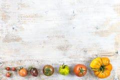 Grens van oude verscheidenheid van tomaten van het kleinst aan het meest bigest op oude witte geschilderde houten achtergrondexem Royalty-vrije Stock Foto