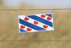 Grensomheining - Oud plastic teken met een vlag Royalty-vrije Stock Foto's