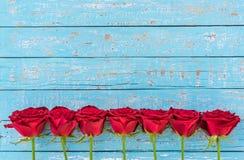Grenze der roten Rosen auf hellblauem Holz, romantische Liebe blüht für Valentinsgruß ` s Tages- oder Hochzeitshintergrund Stockbilder