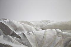 Grenze einer Falte des hellen Seidengewebes auf einem hellen Hintergrund Stockfotografie