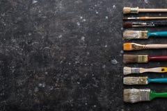 Grenze von alten Pinseln auf dunklem grungy Hintergrund Lizenzfreie Stockfotografie