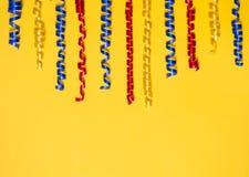 Grenze von farbigen festlichen Bändern auf einem gelben Hintergrund Geschenklandschaft Stockfotografie