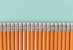 Grenze von orange Bleistiften mit Radiergummis, auf einem blauen grünen Hintergrund mit Kopienraum lizenzfreie stockfotos