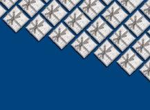 Grenze von silbernen glänzenden Geschenken auf blauem Hintergrund Ökologische, hölzerne Weihnachtsdekorationen Stockfoto