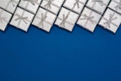 Grenze von silbernen glänzenden Geschenken auf blauem Hintergrund Neues Jahr ` s und Weihnachtsdekorationen Stockfotos