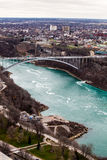 Grenzgrenzregenbogenbrücke Vereinigte Staaten und Kanada, Niagara Falls Schattenbild des kauernden Geschäftsmannes Stockbild