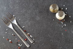 Grey abstract background with forks, salt and pepper shakers. Place for text. Royalty Free Stock Images