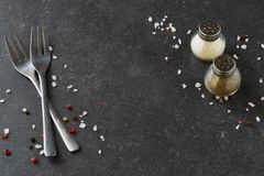 Grey abstract background with forks, salt and pepper shakers. Place for text. Royalty Free Stock Photo
