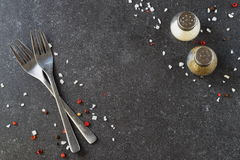 Grey abstract background with forks, salt and pepper shakers. Place for text. Stock Photo