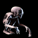 Grey alien crouching in the dark looking mysterious Stock Images