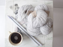 Grey alpaca wool yarns. Bulky gray alpaca wool yarns with big plastic knitting needles, on a white shabby chic table and a cup of coffee aside Royalty Free Stock Photography