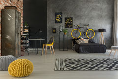 Grey apartment with yellow details. Grey apartment with bed, desk, chair, brick wall, yellow details royalty free stock photography