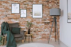 Grey armchair against brick wall. Grey lamp, vase on a stool and dark blanket on grey armchair against brick wall with posters in living room Royalty Free Stock Photo