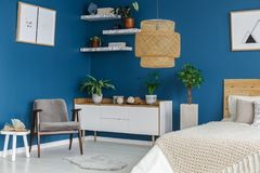 Grey armchair in blue bedroom. Grey armchair next to a white cupboard with plants in blue bedroom interior with posters Stock Photos