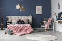 Grey armchair in the corner. Dark grey comfy armchair with cushion and pink blanket in the corner of the room Stock Photography