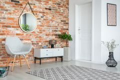 Grey armchair and cupboard in apartment interior with carpet and mirror on red brick wall. Real photo stock image