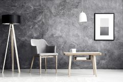 Grey armchair in living room. White lamp above wooden table next to grey armchair in living room interior with poster on concrete wall Royalty Free Stock Images
