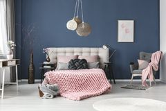 Grey armchair with pink blanket. And pastel pillow in bedroom with subtle painting on blue wall stock photos