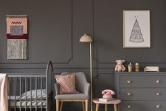 Grey armchair with pink pillow between bed and cabinet in child` stock photo