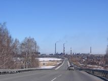 the grey asphalt road leads to an industrial factory on the horizon stock photo