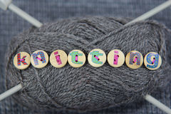 Grey ball of wool with the word knitting spelled in lettered but. Tons sewn to the wool. Knitting needles through wool and grey knitted background Stock Photography