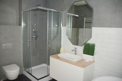 Grey bathroom interior with shower stall with glass walls, mirror bath sink, fauset, wc.  Bathroom interior. Grey bathroom interior with shower stall with glass stock photography