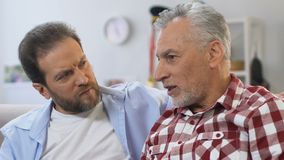 Grey-bearded father telling stories from life to his middle-aged son, relations stock video