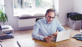 Grey Bearded mature man creative director sitting in modern offi Royalty Free Stock Photo