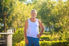 Grey Bearded Old Man in der weißen Weste verbiegt Körper im Park stockfotografie