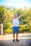 Grey Bearded Old Man in der weißen Weste verbiegt Körper im Park lizenzfreies stockfoto