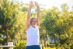 Grey Bearded Old Man in der weißen Weste verbiegt Körper im Park lizenzfreie stockfotos
