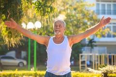 Grey Bearded Old Man in der weißen Weste zeigt Yoga-Haltung im Park stockfotografie