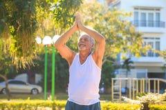 Grey Bearded Old Man in der weißen Weste zeigt Yoga-Haltung im Park lizenzfreie stockbilder