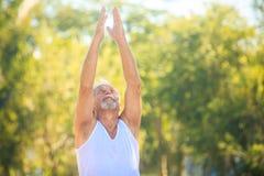 Grey Bearded Old Man in der weißen Weste zeigt Yoga im Park stockfoto