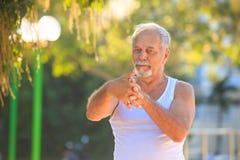 Grey Bearded Old Man in der Weste dehnt Finger im Park aus lizenzfreie stockfotos