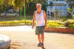 Grey Bearded Old Man in der Weste hält Wasser-Flasche im Park lizenzfreies stockbild