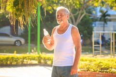Grey Bearded Old Man in der Weste hält Wasser-Flasche im Park lizenzfreies stockfoto