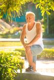 Grey Bearded Old Man in der Weste setzte Bent Leg auf Bank in Park ein lizenzfreies stockbild
