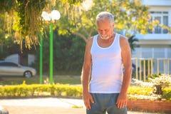 Grey Bearded Old Man en chaleco estira los fingeres en parque fotografía de archivo