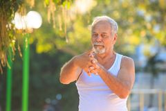 Grey Bearded Old Man en chaleco estira los fingeres en parque fotos de archivo libres de regalías